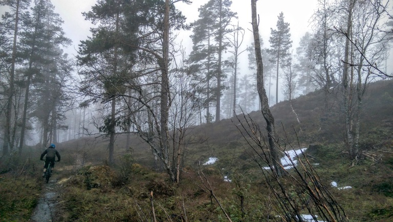 riding singletrack on the enduro bike in the mist above kaupanger