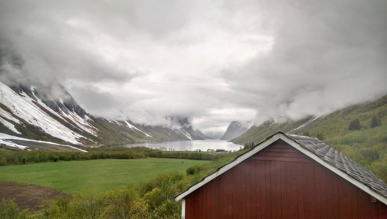 red norwegian cabin standing at top of valley with fjord and cloudy sky
